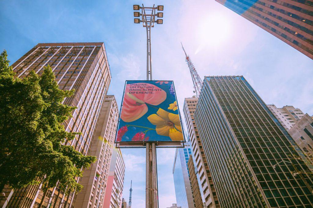 """Banner fixado em um dos postes de iluminação da Avenida Paulista. A imagem no banner é de flores coloridas, feita por um dos artistas que participaram da exposição """"Imagine 2030 na Virada Sustentável de São Paulo."""""""