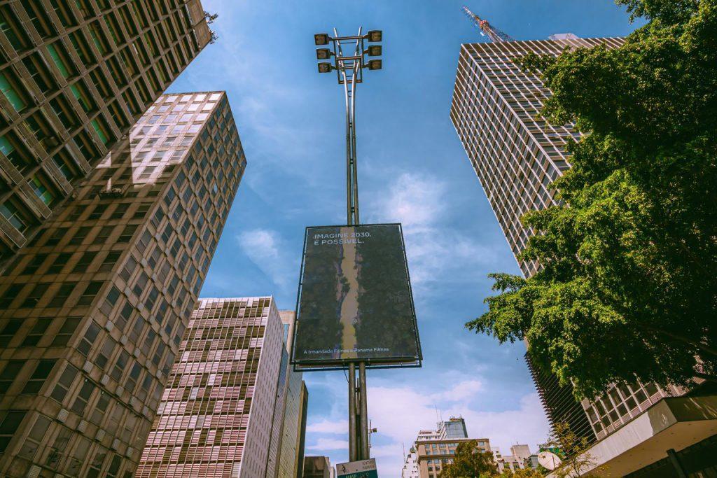 Banner fixado em um dos postes de iluminação da Avenida Paulista. A imagem no banner contém árvores e um rio que as divide, lembrando uma imensa floresta. A imagem foi feita por um dos artistas que participaram da exposição.