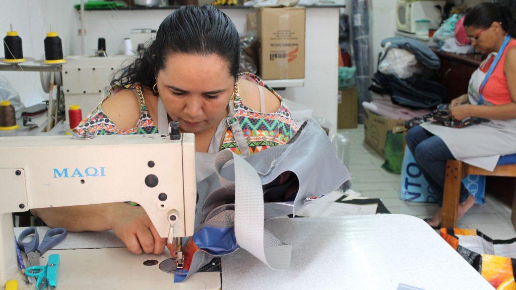 """Uma costureira do """"Cardume de Mães"""" manuseando a máquina e utilizando o material da lona para transformar em bolsa."""