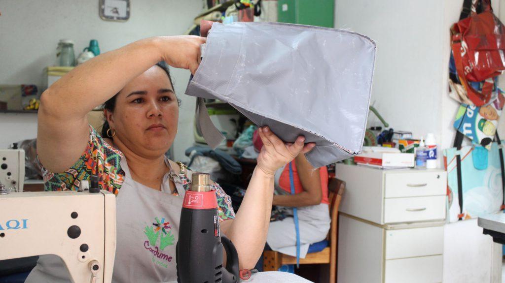 A costureira aparece segurando uma bolsa cinza quase pronta.