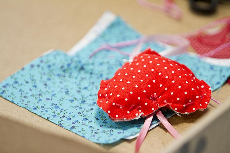 Broche de coração vermelho com bolinhas brancas em cima da mesa.