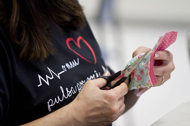 Tecidos sendo cortados em formato de coração.